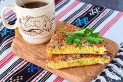 Twee stukken van witte koolpastei met wortel op een zwarte plaat met kop thee en de rest van de pastei op een textiel Stock Afbeelding