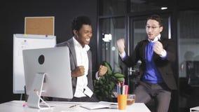 Twee Succesvolle en businessmans die dient het bureau in juming opheffen stock videobeelden