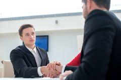 Twee succesvolle en gemotiveerde zakenlieden schudden handen Stock Foto's