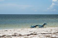 Twee sunbeds door de waterlijn Royalty-vrije Stock Fotografie