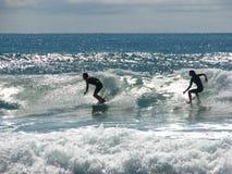 Twee surfers die een golf berijden. Stock Foto's