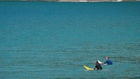 Twee surfers die op grote golven wachten stock footage