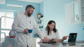 Twee tandartsen artsen bespreken tandct aftasten gebruikend laptop in de kliniek stock footage