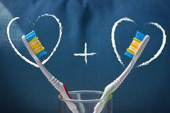 Twee tandenborstels op een blauwe achtergrond en twee harten met een plusteken royalty-vrije stock fotografie