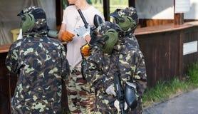 twee teams van paintballspelers in camouflage vormen zich met maskers, helmen, kanonnen op het gebied in de zomer het actieve spo royalty-vrije stock foto's