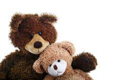 Twee teddyberen die, groter en kleiner, dicht bij elkaar zitten als zijn zij beste vrienden. Stock Foto