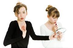 Twee teenaged meisjes kibbelen om een spiegel ertoe te brengen om een merk omhoog te maken - zusterrivaliteit royalty-vrije stock foto's