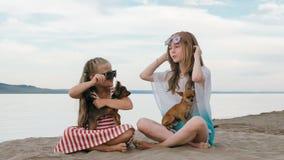 Twee tiener zitten op een zandig strand dichtbij het overzees Zij hebben twee honden Royalty-vrije Stock Fotografie