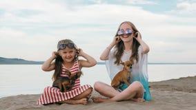 Twee tiener zitten op een zandig strand dichtbij het overzees Zij hebben twee honden Stock Foto's