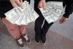 Twee tienerjaren die met funs van dollars in handen blijven Stock Fotografie