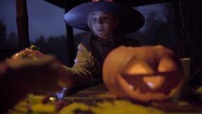 Twee tienermeisjes die candys na truc delen of behandelen op Halloween-nacht stock videobeelden