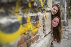 Twee tienermeisjes kijken uit van achter de hoek van een steenhuis Royalty-vrije Stock Foto