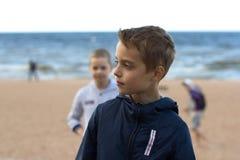 Twee tieners bevinden zich op het strand door het overzees De broers lopen al Royalty-vrije Stock Fotografie