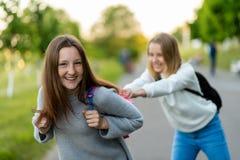 Twee tieners De schoolmeisjes spelen na het instituut Het gelukkige glimlachen houdt elkaar voor rugzakken Emoties van royalty-vrije stock afbeelding