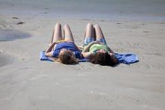 Twee Tieners die bij het Strand zonnebaden Stock Afbeelding