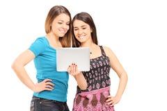 Twee tieners die een tablet bekijken stock foto's