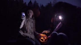 Twee tieners die met lichten op Halloween-nacht spelen stock footage