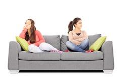 Twee tieners die op bank boos met elkaar zitten stock afbeelding