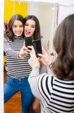 Twee tieners die selfie beelden voor de spiegel nemen royalty-vrije stock afbeelding