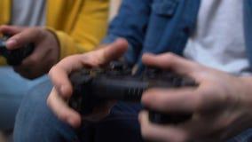 Twee tieners die snelle videospelletjes spelen, en vuisten winnen dichtklemmen stock videobeelden