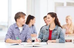 Twee tieners met notitieboekjes en boek op school Stock Foto