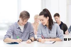 Twee tieners met notitieboekjes op school Royalty-vrije Stock Afbeeldingen