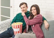 Twee tieners zitten op de laag lettend op TV stock foto's