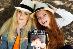 Twee tienersmeisje die selfe met camera nemen Stock Afbeeldingen