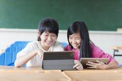 Twee tienersstudent die op de tablet in klaslokaal letten royalty-vrije stock foto's