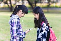 Twee tienersvrienden die op de slimme telefoon in school letten Stock Afbeeldingen