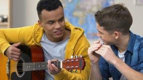 Twee tienervrienden genieten van speel gitaar en harmonika samen, muzikale hobby stock videobeelden
