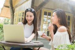 Twee tienervrouwen komen in het gebruikslaptop van de koffiewinkel samen samen binnen achterin stock foto's