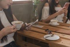 Twee tienervrouwen komen in sociale samen het spel van het gebruikssmartphone van de koffiewinkel royalty-vrije stock foto's