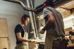 Twee timmerlieden die hout met figuurzaag snijden royalty-vrije stock fotografie