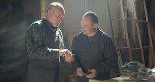 Twee timmerwerkmeesters die zich in het hout bevinden vervaardigen het bespreken van materiaal het letten op op kopspijkers stock footage