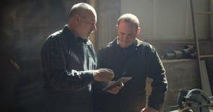 Twee timmerwerkmeesters die zich in het hout bevinden vervaardigen het bespreken van proces het letten op in tablet stock video