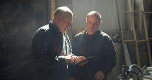 Twee timmerwerkmeesters die zich in het hout bevinden vervaardigen het bespreken van het werkplan in tablet stock video