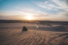 Twee toeristen berijden op vierlingfiets op zandduin op de achtergrond van een mooie dageraad met een heldere zon vroeg in de och royalty-vrije stock foto's