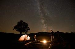 Twee toeristen bij het branden van kampvuur voor tent, fotocamera op driepoot onder donkere sterrige hemel stock afbeelding