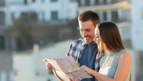 Twee toeristen die een document gids raadplegen over vakantie stock footage