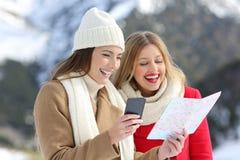 Twee toeristen die een kaart in de wintervakantie lezen Royalty-vrije Stock Foto