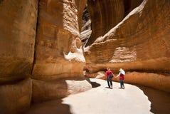 Twee toeristen die langs de kloof van Petra lopen Stock Fotografie