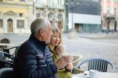 Twee toeristen die op middelbare leeftijd koffie in koffie met terras in openlucht in de oude stad in de ochtend drinken tijdens  royalty-vrije stock afbeeldingen