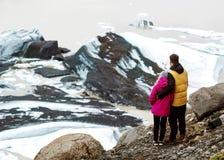 Twee toeristen zullen op een ijsberg in IJsland zijn stock afbeelding