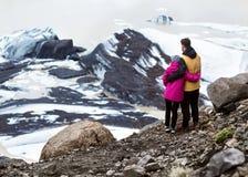 Twee toeristen zullen op een ijsberg in IJsland zijn stock foto's