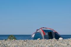 Twee toeristententen op een kiezelsteen overzeese kust in de ochtend royalty-vrije stock fotografie