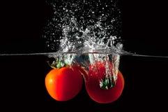 Twee tomaten die in water vallen Royalty-vrije Stock Afbeeldingen