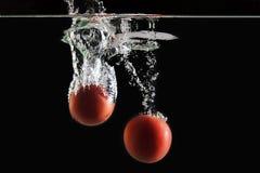 Twee tomaten die in water vallen Stock Afbeeldingen