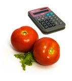 Twee tomaten en calculator Stock Afbeeldingen