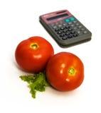 Twee tomaten en calculator stock afbeeldingen